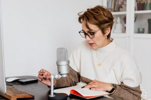 woman narrating story while recording audiobook