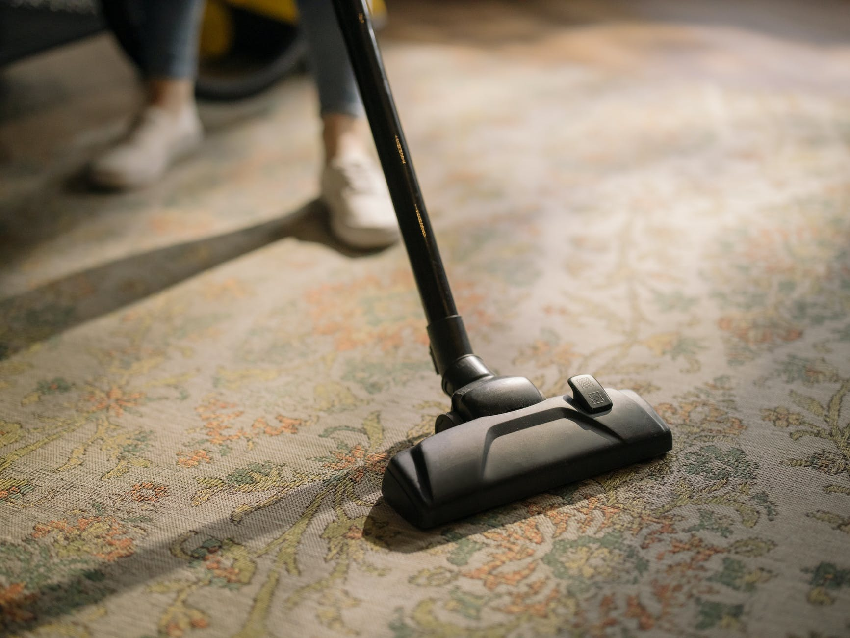 black vacuum cleaner on brown and white area rug