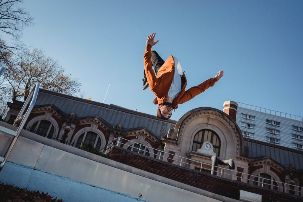 athlete showing back flip in air in town